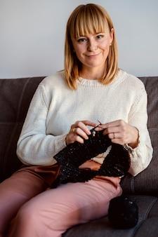 Mulher tricotando um acessório de fio preto vista frontal