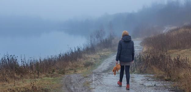 Mulher triste adolescente com urso de pelúcia na estrada rural pelo lago nevoento. conceito de adolescência e problemas do adolescente.