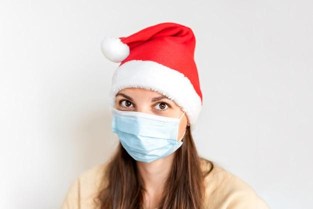 Mulher triste caucasiana com máscara médica e chapéu de papai noel. natal sozinho em quarentena