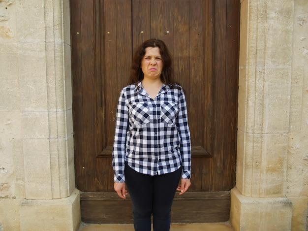 Mulher triste chorando no fundo da porta fechada.