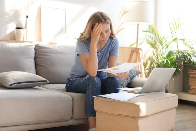 Mulher triste com as contas, sentado em um sofá na sala de estar.