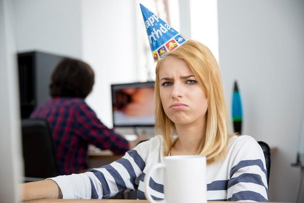Mulher triste com chapéu de aniversário sentada à mesa
