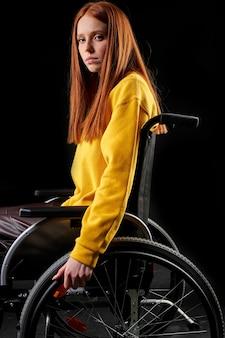 Mulher triste com deficiência em uma cadeira de rodas, deprimida. mulher ruiva na camisa amarela casual fica isolada na parede preta. conceito de saúde e pessoas