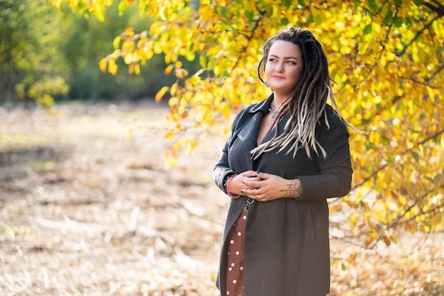Mulher triste com dreads ao ar livre no outono, conceito de cultura jovem