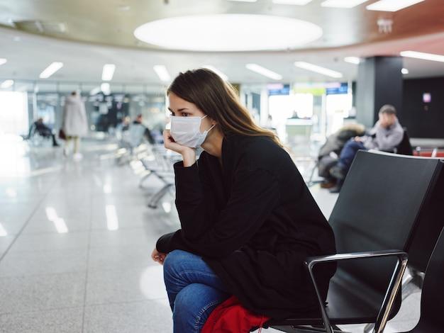 Mulher triste com máscara médica esperando atraso de voo do aeroporto