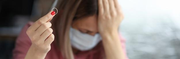 Mulher triste com máscara protetora segurando a aliança na mão