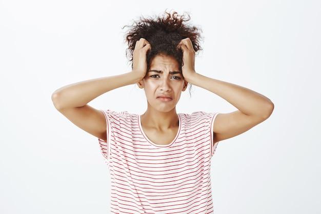 Mulher triste com penteado afro posando no estúdio