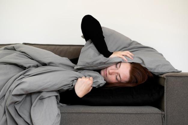 Mulher triste com tiro médio deitada no sofá