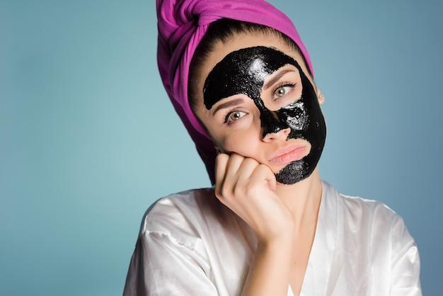 Mulher triste com uma toalha na cabeça depois de tomar banho com uma máscara no rosto