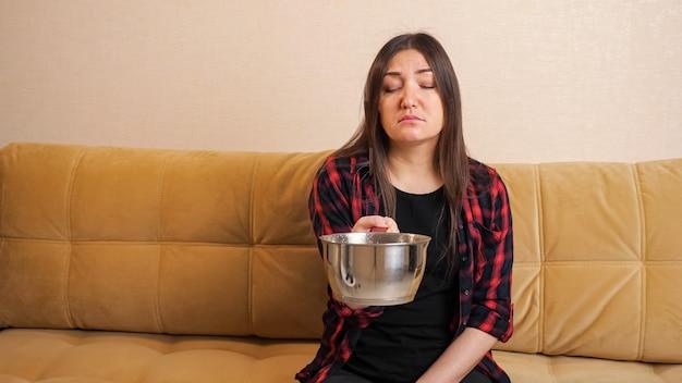 Mulher triste de cabelos compridos e camisa quadriculada coleta água que flui do teto para a panela, sentada em um sofá confortável na sala de estar moderna