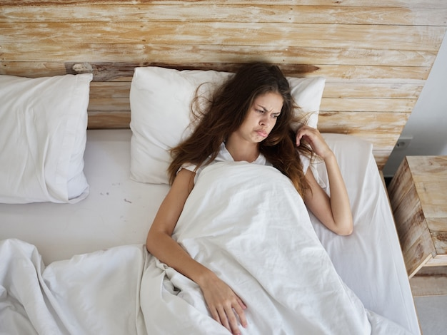 Mulher triste deitada na cama com beicinho