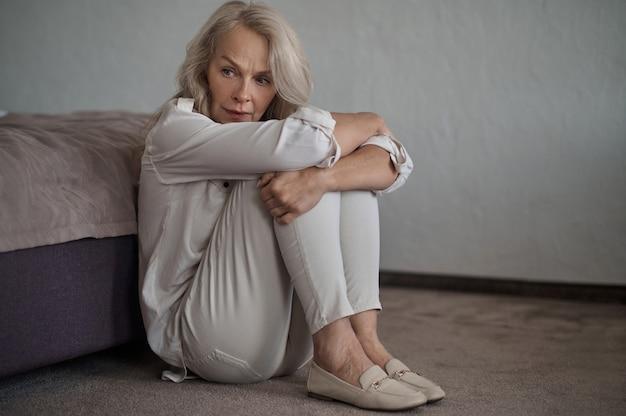 Mulher triste e assustada sentada no chão acarpetado ao lado da cama e abraçando os joelhos
