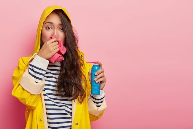 Mulher triste e chateada esfrega o nariz com um lenço, apresenta sintomas de doença sazonal, segura spray para dor de garganta, resfriou-se após ficar ao ar livre em tempo chuvoso