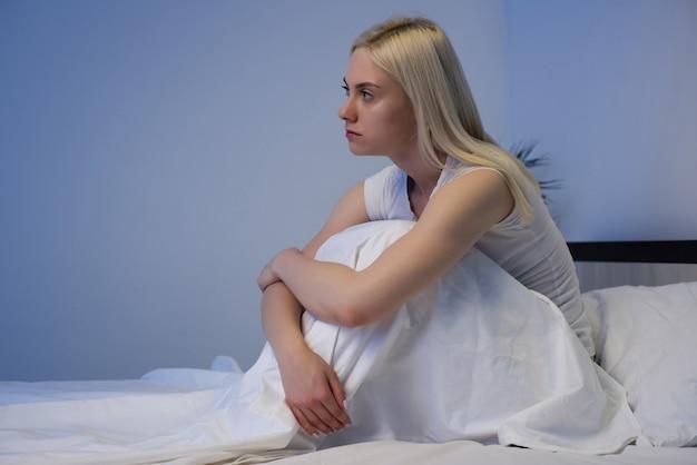 Mulher triste e deprimida sentada em sua cama tarde da noite, ela está pensativa e sofrendo de insônia