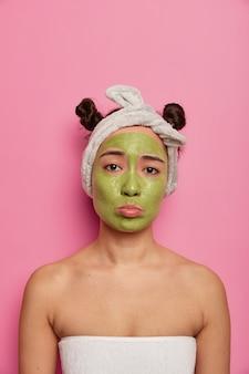 Mulher triste e descontente recebe tratamento facial com máscara verde no rosto
