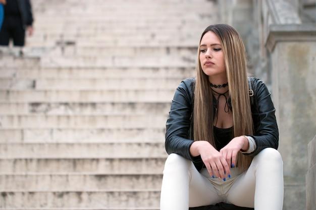 Mulher triste e entediada pensando em alguma coisa.