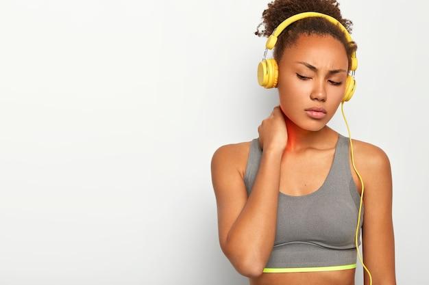 Mulher triste e esportiva sofre de dores no pescoço, tem sensações desagradáveis, toca a área problemática