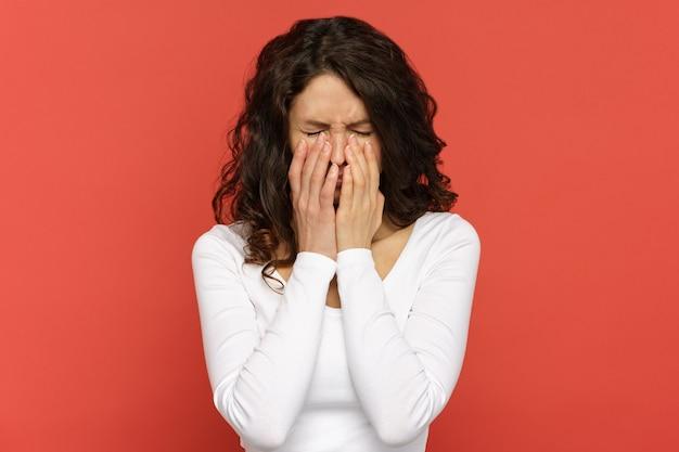 Mulher triste e infeliz esconde o rosto nas mãos, chora jovem deprimida com os olhos fechados, assustada ou chateada