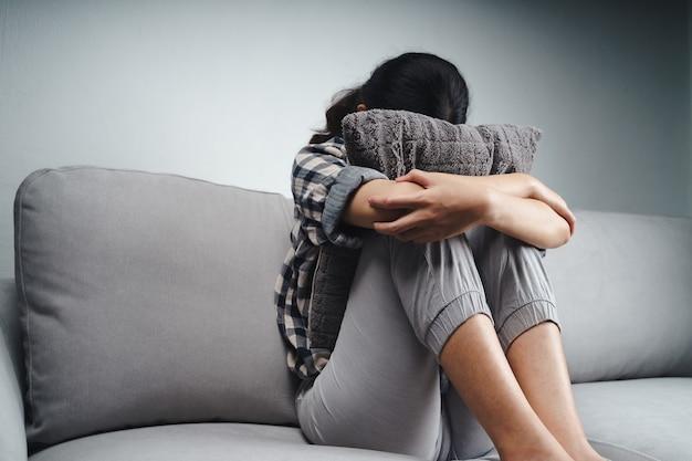 Mulher triste e solitária infeliz está sentada no sofá e escondendo o rosto em um travesseiro, conceito de depressão