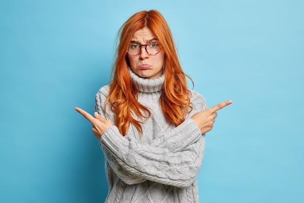 Mulher triste e sombria com cabelo ruivo cruza os braços e aponta para diferentes direções tenta pegar algo entre dois itens de bolsas de lábio inferior vestidas de suéter de malha cinza.