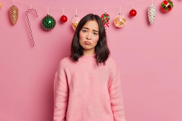 Mulher triste e sombria com cabelos escuros usando macacão casual parece infeliz para a câmera estragou o clima na véspera de natal porque os convidados não apareceram na festa