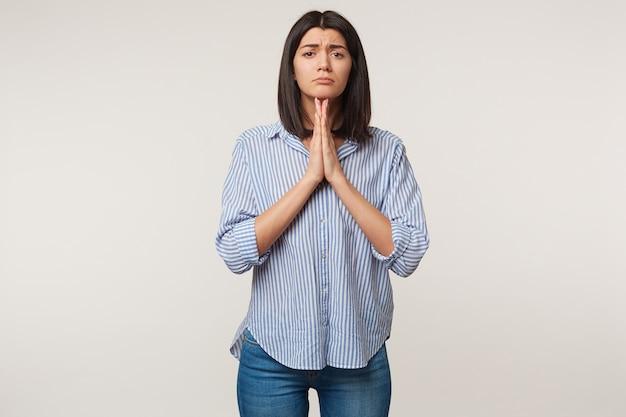 Mulher triste e triste cruzou as mãos em gesto de oração e olha com esperança, ora por uma pessoa próxima, quer algo, precisa de outra chance, espera pela sorte,