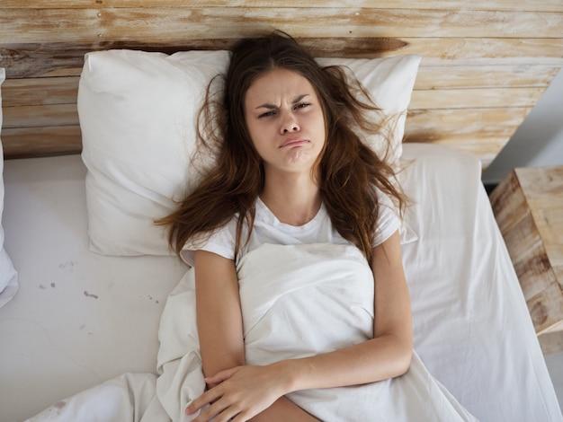 Mulher triste e triste deitada na vista de cima da cama