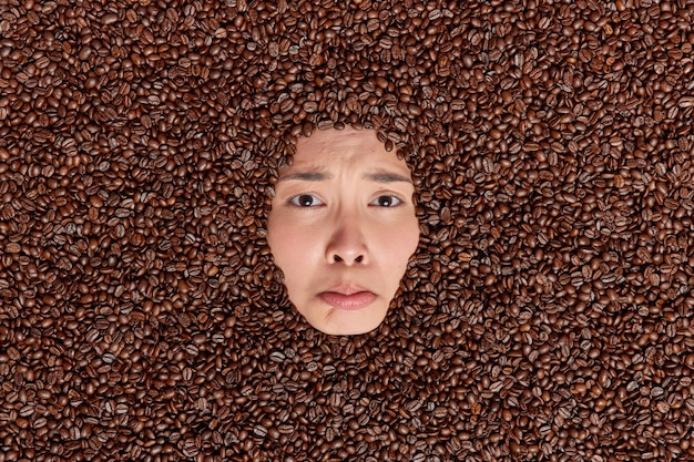 Mulher triste e triste mostrando apenas o rosto através dos grãos de café