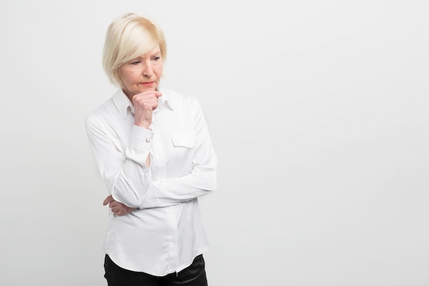 Mulher triste e velha está pensando em alguma coisa. ela tem alguns problemas com a saúde, por isso não parece nada confiante. cortar vista.