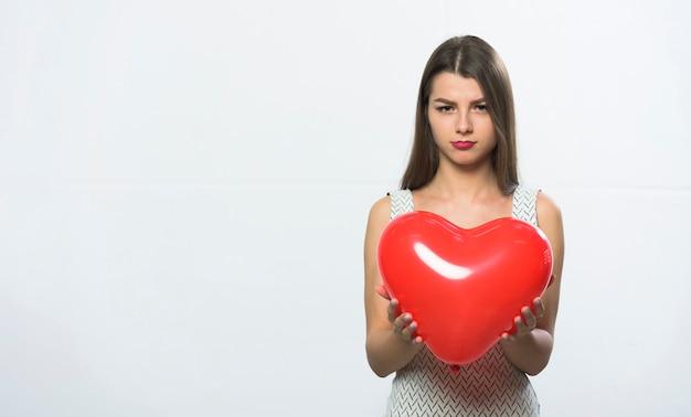 Mulher triste em pé com balão de coração vermelho