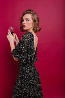 Mulher triste em um vestido longo elegante olhando por cima do ombro, segurando um copo de vinho