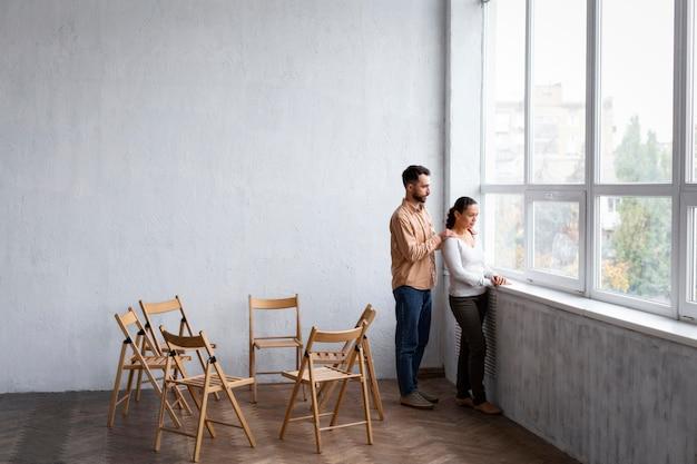 Mulher triste olhando pela janela em uma sessão de terapia de grupo com um homem consolando-a