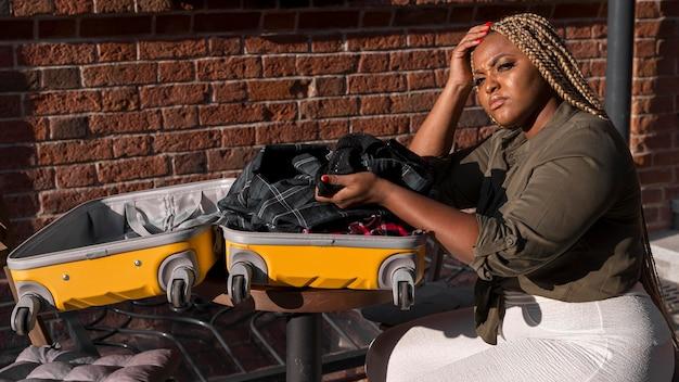 Mulher triste olhando sentada ao lado de sua bagagem aberta