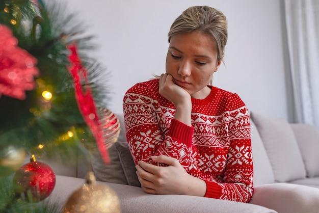 Mulher triste pela árvore de natal contemplando