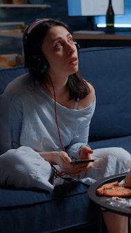 Mulher triste, pensativa, ansiosa, ouvindo música usando um smartphone, sentindo-se solitária e preocupada com ...