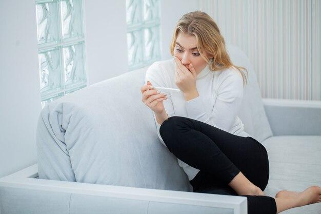 Mulher triste preocupada, olhando para um teste de gravidez após o resultado.