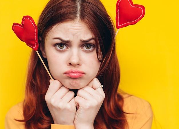 Mulher triste segurando objetos em forma de coração para o dia dos namorados