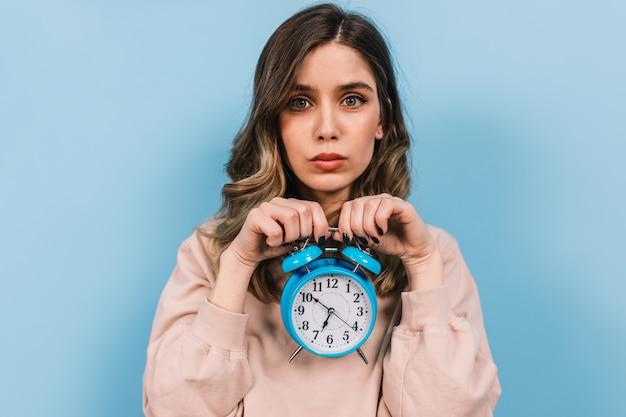 Mulher triste segurando um grande relógio