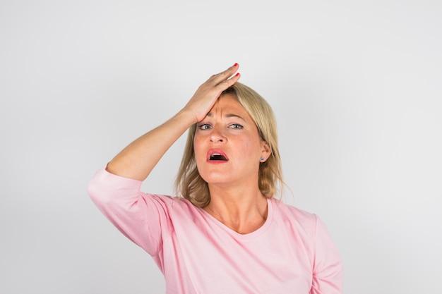 Mulher triste sênior na blusa rosa