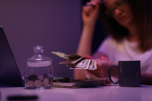Mulher triste sentada à mesa em um quarto escuro e contando dinheiro para closeup de contas de serviços públicos. conceito de crise econômica