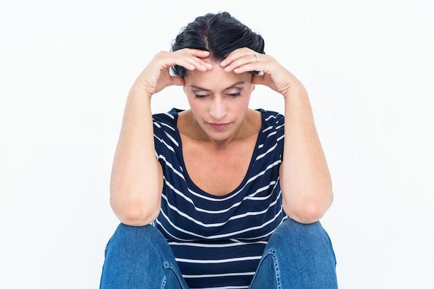Mulher triste sentada com a cabeça nas mãos