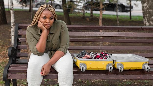 Mulher triste sentada em um banco ao lado de sua bagagem aberta