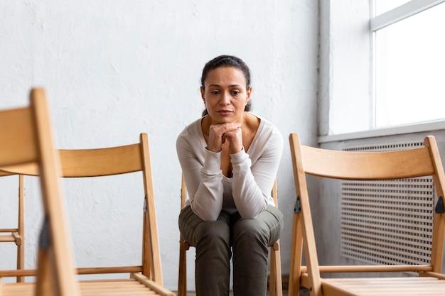 Mulher triste sentada em uma cadeira em uma sessão de terapia de grupo