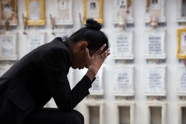 Mulher triste sentada perto de um túmulo