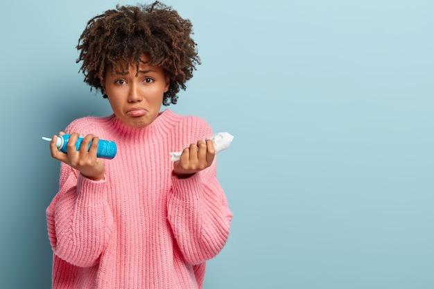 Mulher triste sofre de alergia sazonal, segura lenço e aerossol nasal, tem penteado afro, usa um macacão rosa grande demais, modelos sobre parede azul com espaço em branco para seu texto