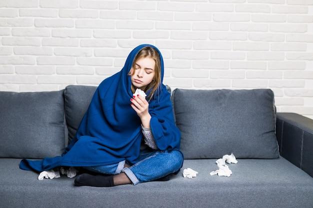 Mulher triste, triste e cansada, sentada em um sofá em casa, resfriada e usando guardanapos, fica resfriada