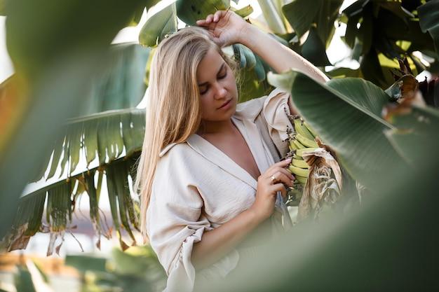 Mulher tropical exótica perto de folhas verdes de arbusto de bananeira. garota da ilha tropical de férias