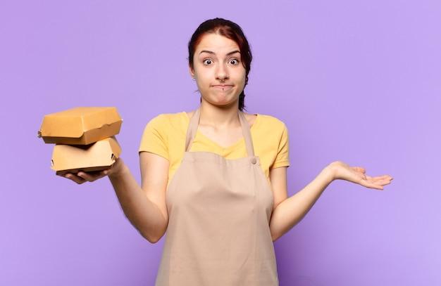 Mulher tty com um avental. conceito de entrega de hambúrguer para levar