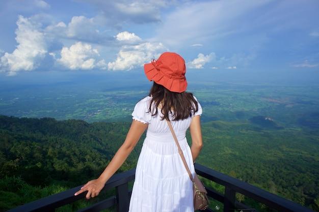 Mulher turista asiática com vestido branco e chapéu laranja escuro nas costas, de pé e observando a bela vista da montanha e do céu do terraço em phu thap berk, tailândia, conceito de estilo de vida
