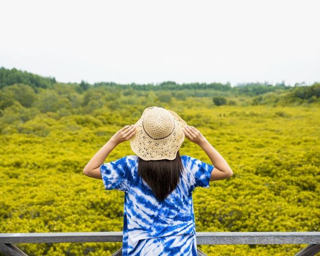 Mulher turista asiática segurando o chapéu e em pé na ponte de madeira na cidade de pak nam prasae local da floresta de tung prong thong em rayong, tailândia.
